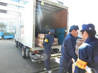 備蓄倉庫から救援物資を積み込む輸送隊員